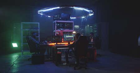 Medium shot of young men hacking in a dim basement