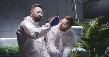 Medium shot of two male scientists examining soil of Martian garden