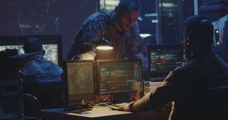 Mittlere Aufnahme eines Soldaten, der an einem Computer arbeitet Standard-Bild
