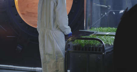 Medium shot of a scientist in hazmat suit pushing cart of seedlings and checking plant incubators on a Mars base