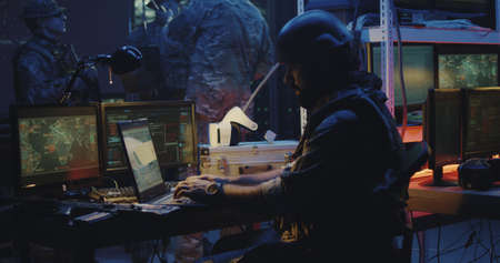 Medium shot of a soldier working on a laptop in full combat gear