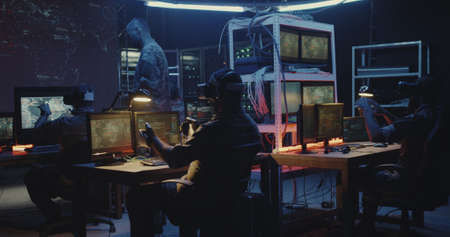 Medium shot of soldiers using VR technology while sitting at their desks
