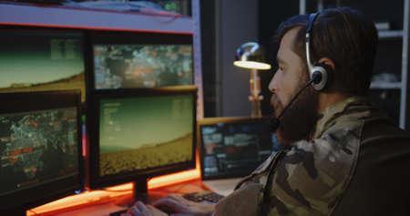 Primer plano medio de un soldado que supervisa el lanzamiento de un cohete en la computadora