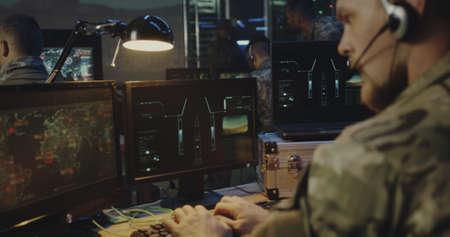 Mittlere Nahaufnahme von Soldaten, die den Raketenstart auf dem Computer steuern