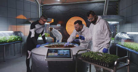 Medium shot of scientists examining seedlings before planting them on a Mars base