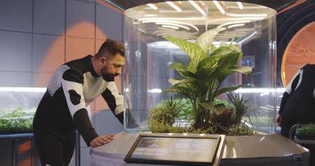 Medium shot of a male astrobiologist looking at camera while leaning on a plant incubator on a Mars base Banco de Imagens