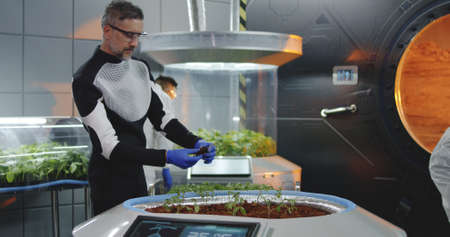 Medium shot of a a scientist planting seedlings on a Martian base