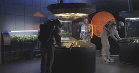Medium shot of astronauts and humanoid robot examining plant incubators on a Mars base