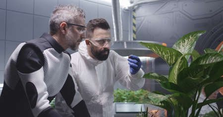 Medium shot of male scientists examining soil of Martian garden Banque d'images