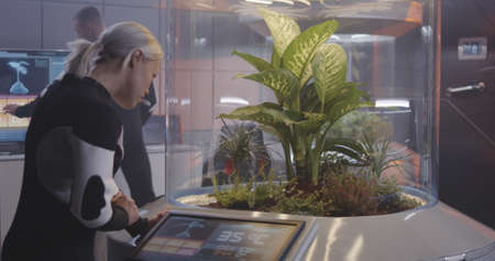 Medium shot of a female scientist using digital interface of a plant incubator