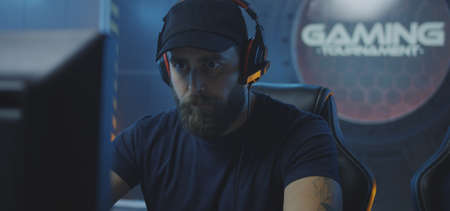 Medium close-up of a young bearded man playing at a gaming tournament