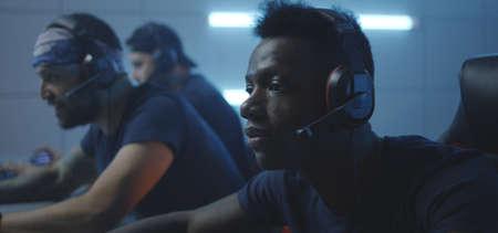 Medium close-up of young men playing at a gaming tournament