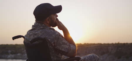 Medium shot of a depressed soldier sitting in a wheelchair on a meadow at sunset