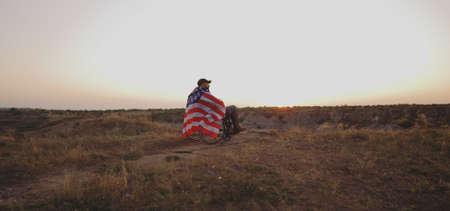 Plan large d'un soldat américain en fauteuil roulant regardant le coucher du soleil sur un pré Banque d'images
