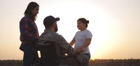 Full shot of a wheelchaired soldier kissing his wife and hugging his daughter on a meadow Фото со стока