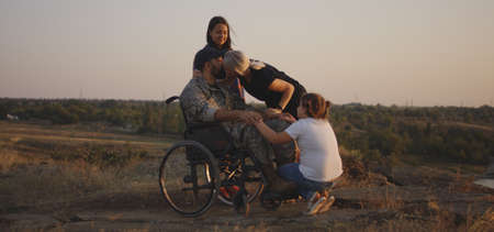 Full shot of a wheelchaired soldier kissing his wife and hugging his daughter on a meadow