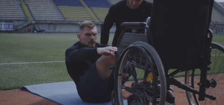 Full shot of a disabled male athlete doing sit ups while being encouraged by trainer