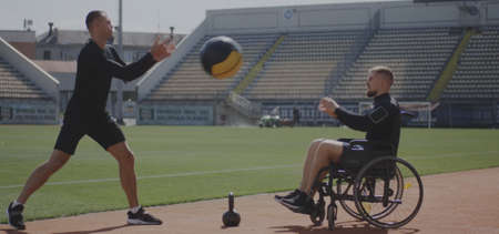 Full shot of a wheelchaired athlete and his trainer working out with a medicine ball Stockfoto