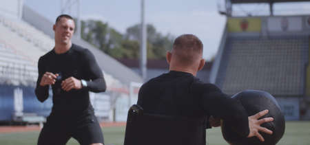Medium shot of a wheelchaired athlete and his trainer working out with a medicine ball