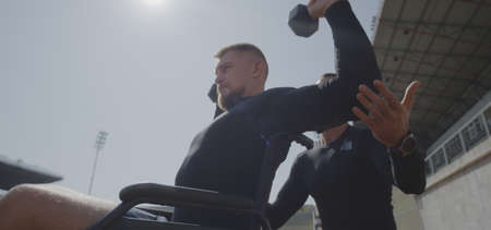 Medium shot of a wheelchaired young man doing overhead presses with dumbbells while his trainer assisting him Banco de Imagens