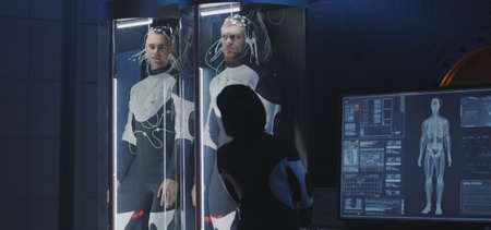Medium shot of a female scientist studying human biology in a Martian laboratory with two young male subjects in stasis pods Stock fotó