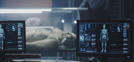Medium shot of scientists studying human biology in a Martian laboratory with young male subjects lying in incubators Stock fotó