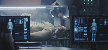 Medium shot of scientists studying human biology in a Martian laboratory with young male subjects lying in incubators