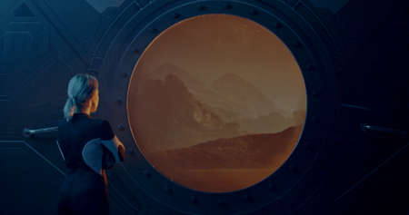 Medium shot of a female astronaut looking out of the window of a Martian base Stok Fotoğraf