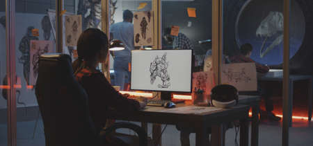 Medium shot of a young woman drawing game art on computer Stock fotó