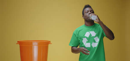 Medium shot of man drinking from plastic bottle than recycling it against yellow background
