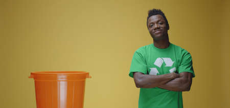 Medium shot of man standing firm while wearing t shirt with recycling symbol on it against yellow background Stock Photo