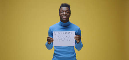 Medium shot of young man holding sign with discount written on against yellow background 스톡 콘텐츠