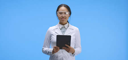 Medium shot of a young female scientist looking at camera and holding digital tablet computer in hands