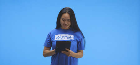 Medium shot of a young female volunteer using a tablet and smiling at camera