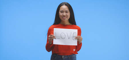Medium shot of a young woman holding up love sign Imagens