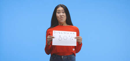 Medium shot of a young woman holding a special offer price sign with eighty percent discount