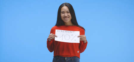 Medium shot of a young woman holding a special offer price sign with ten percent discount Imagens