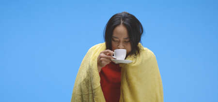 Medium shot of sick woman drinking the against blue background Imagens