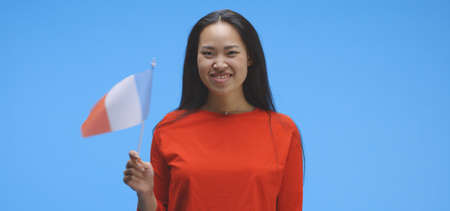 Medium shot of young woman waving with french flag against blue background