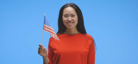 Medium shot of young woman waving with US flag against blue background