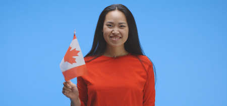 Medium shot of young woman waving with Canadian flag against blue background