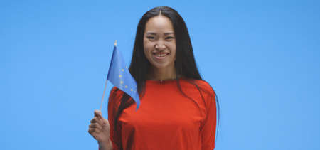Medium shot of young woman waving with EU flag against blue background Imagens