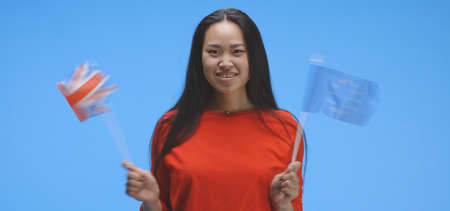 Medium shot of young woman waving with EU and UK flag against blue background