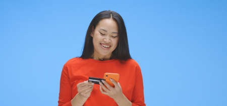 Medium shot of young woman buying on internet against blue background Stock Photo