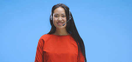 Medium shot of young woman talking while wearing headset against blue background
