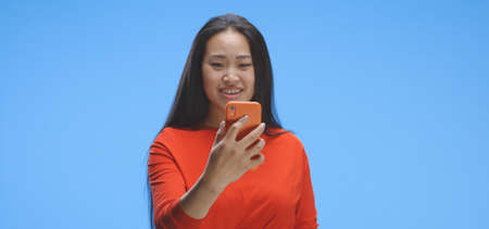 Medium shot of young woman video chatting with smartphone against blue background Imagens