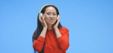 Medium shot of young woman listening to music on headphones against blue background