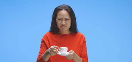 Medium shot of young woman drinking coffee against blue background