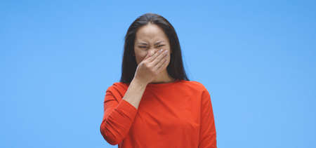 Medium shot of young woman experiencing bad smell against blue background