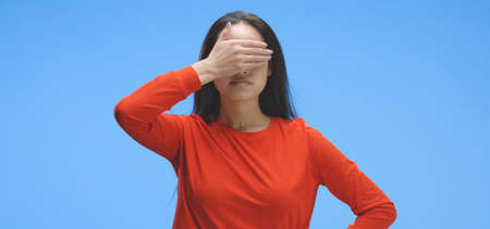 Medium shot of young woman covering eyes against blue background